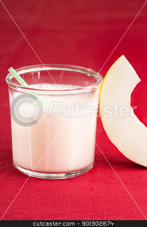 Melon Smoothie stock photo, A sweet melon smoothie on a red cloth by Tyler Olson