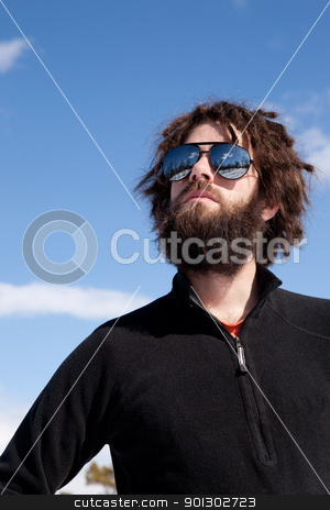 Winter Portrait stock photo, A male with a full beard and retro sunglasses standing in a winter landscape ready for adventure by Tyler Olson