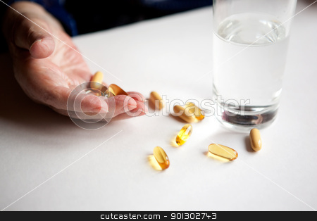 Pills stock photo, An elderly hand with a variety of large pills by Tyler Olson