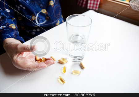 Old Hand with Pills stock photo, An elderly hand with a variety of large pills - shallow depth of field, focus on hand and pills by Tyler Olson