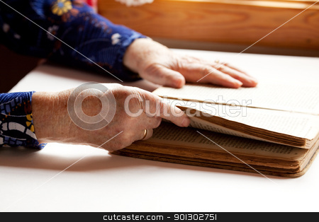 Elderly Reading stock photo, An old pair of hands holding the pages in a book, reading. by Tyler Olson