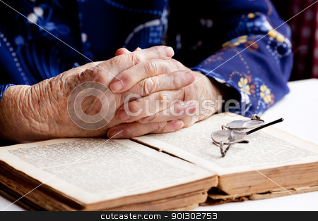 Hands Praying stock photo, An old pair of hands in prayer on a book by Tyler Olson