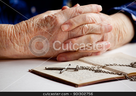 Old Faith stock photo, Old female hands with a cross and book by Tyler Olson
