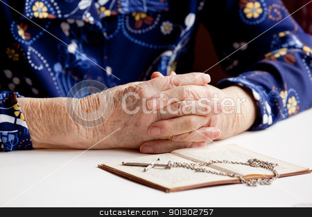Prayer stock photo, Old folded hands in front of a book and cross.  Focus on the hands. by Tyler Olson