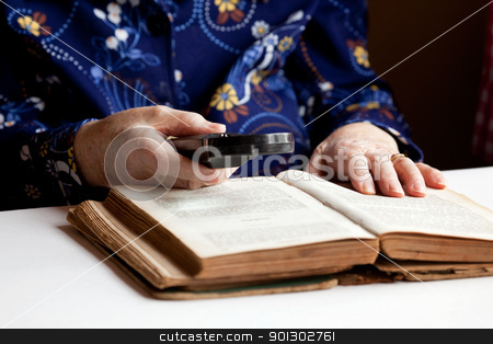 Elderly Woman Reading stock photo, An elderly woman reading a very old book by Tyler Olson