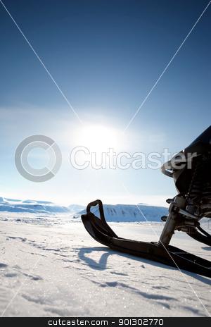 Snowmobile stock photo, Snowmobile against a deep blue sky by Tyler Olson