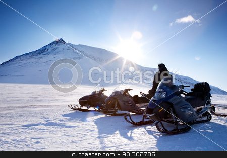 Snowmobile Adventure stock photo, Three snowmobiles and a winter landscape with mountain by Tyler Olson
