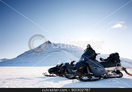 Three snowmobiles and a winter landscape with mountain stock photo, Snowmobile Adventure by Tyler Olson