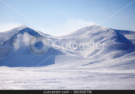 Snow Covered Mountain stock photo, A mountain with blowing snow in a winter landscape by Tyler Olson