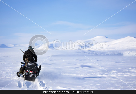 Winter Snowmobile Landscape stock photo, A winter landscape with a snowmobile travelling across frozen ice by Tyler Olson