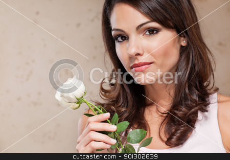 Attractive young female holding a white rose stock photo, An attractive young female holding a white rose by Tyler Olson