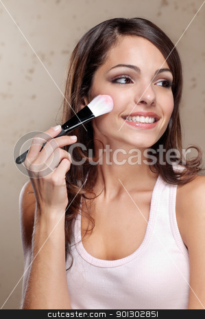 Young woman applying cosmetic paint brush stock photo, Pretty young woman applying cosmetic paint brush by Tyler Olson