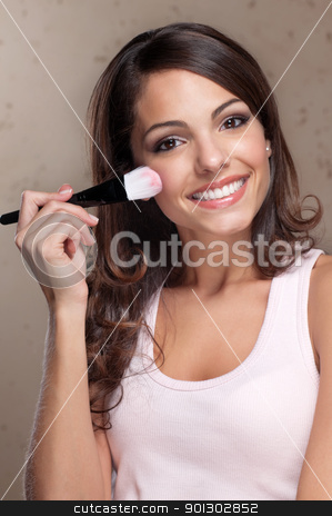 Pretty young woman applying blusher stock photo, Portrait of pretty young woman applying cosmetic paint brush by Tyler Olson