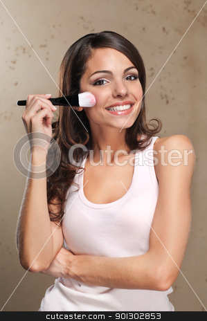 Woman applying blusher stock photo, Portrait of an attractive young adult woman applying blusher by Tyler Olson