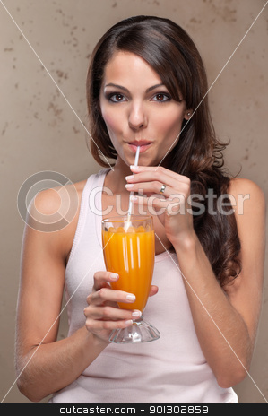 Woman drinking orange juice stock photo, Portrait of pretty young woman drinking orange juice by Tyler Olson