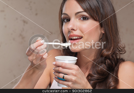 Woman with yogurt stock photo, Portrait of young female eating yogurt by Tyler Olson