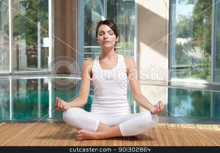Woman doing yoga exercise stock photo, Pretty young woman with eyes closed doing yoga exercise on mat by Tyler Olson