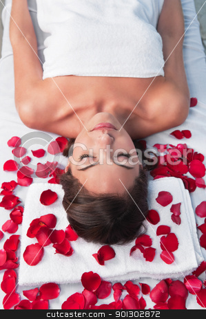 Relaxed woman lying on a massage table stock photo, Relaxed woman lying on a massage table in a spa center with rose petals around by Tyler Olson