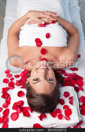 Smiling beautiful woman lying on a massage table stock photo, Smiling beautiful woman lying on a massage table with rose petals around by Tyler Olson