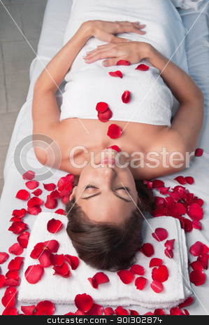 Beautiful relaxed woman lying on a massage table stock photo, Beautiful relaxed woman lying on a massage table with rose petals around by Tyler Olson