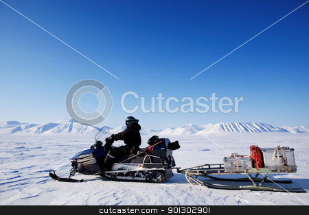 Snowmobile expedition stock photo, A snowmobile on an arctic expedition on a frozen lake by Tyler Olson