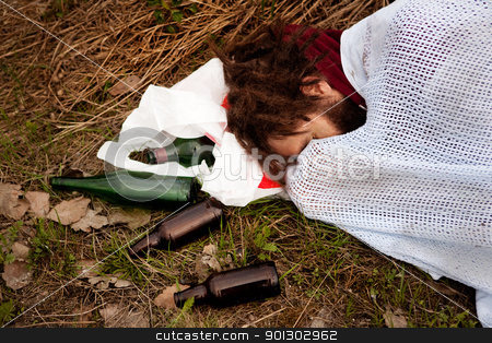 Drunk stock photo, A person drunk sleeping in the ditch with liquor bottles by Tyler Olson