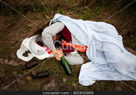 Drunk Person stock photo, A homeless drunk person laying by the edge of the road by Tyler Olson