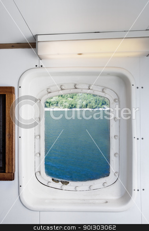 Ship Port Detail stock photo, A ship port window looking out on a coast by Tyler Olson