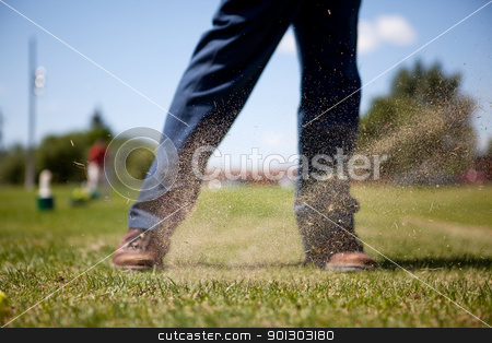 Golf Swing stock photo, A golf swing on a driving range with sand in the air by Tyler Olson