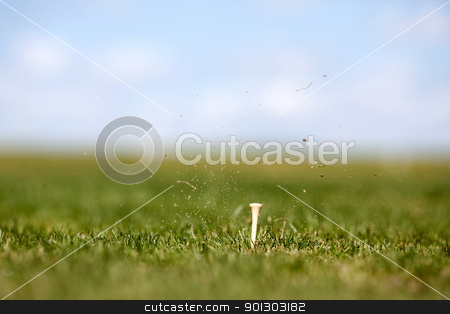 Golf Swing stock photo, The after effects of a golf swing.  Shallow depth of field with focus on the tee by Tyler Olson