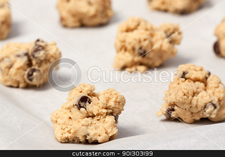 Raw Cookie Dough stock photo, Raw cookie dough on a baking sheet with parchment by Tyler Olson