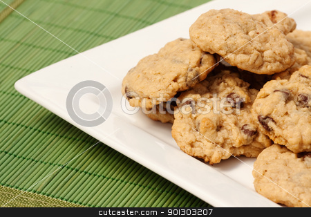 Plate of Cookies stock photo, A plate of oatmeal chocolate chip cookies on a green mat by Tyler Olson