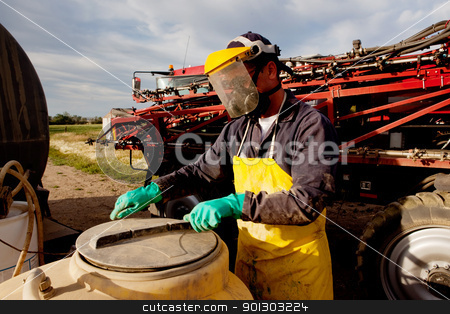 Chemical Safety stock photo, Filling a high clearance sprayer with chemical and water with proper safety equipment by Tyler Olson