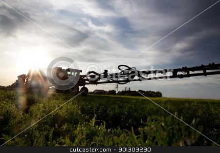 High Clearance Sprayer stock photo, A silhouette of a high clearance sprayer on a field with solar flare. by Tyler Olson