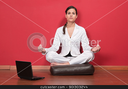 Businesswoman sitting in yoga lotus position stock photo, Young businesswoman sitting in yoga lotus position with laptop on the floor by Tyler Olson