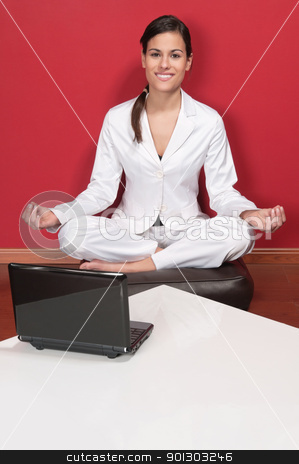 Smiling businesswoman sitting in yoga lotus position stock photo, Attractive businesswoman sitting in yoga lotus position with laptop on table by Tyler Olson