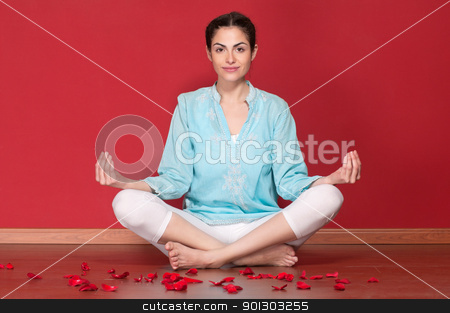Young beautiful female practicing yoga stock photo, Portrait of young beautiful female practicing yoga with rose petals on floor by Tyler Olson