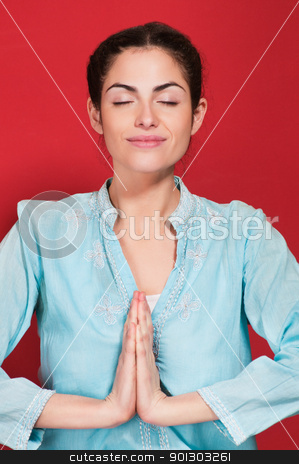 Young woman with hands clasped stock photo, Smiling young woman with hands clasped against red background by Tyler Olson