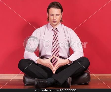 Businessman meditating on the floor stock photo, Relaxed businessman sitting on the floor by Tyler Olson