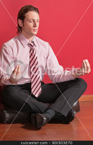 Smart businessman sitting in yoga lotus position stock photo, Smart businessman sitting in yoga lotus position on the floor by Tyler Olson