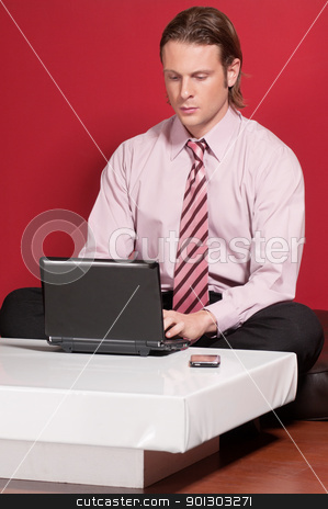 Concentrated businessman using a laptop stock photo, Concentrated businessman using a laptop while sitting on a floor by Tyler Olson
