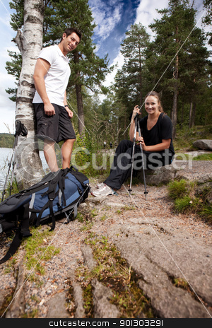 Camping Couple stock photo, A couple hiking in the woods taking a break by the lake by Tyler Olson