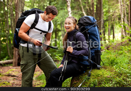 Happy Campers stock photo, A couple with smiles looking at a map in the forest by Tyler Olson