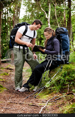 Backpack Couple stock photo, A couple on a backpacking camping trip looking at a map by Tyler Olson