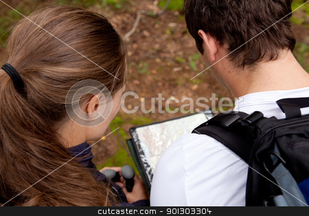 Orienteering Couple stock photo, A couple orienteering with a map while camping by Tyler Olson