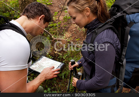 Lost Camping Couple stock photo, A coupld with map and compass in the forest - lost by Tyler Olson