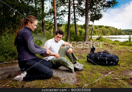 First Aid stock photo, A woman applying an arm bandage on a male camper by Tyler Olson