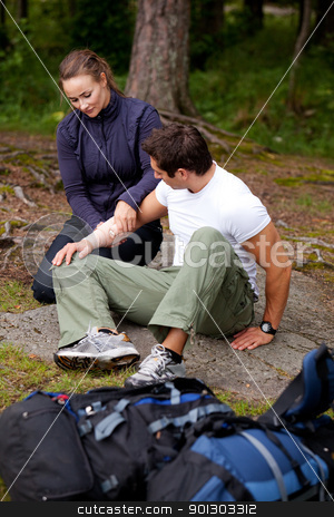 Camping First Aid stock photo, A woman applying an arm bandage on a male camper - focus on male face by Tyler Olson