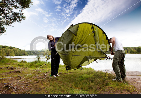 Tent stock photo, A couple setting up a tent in the forest by a lake by Tyler Olson