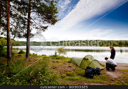 Camping by Lake stock photo, A couple camping on a lake landscape by Tyler Olson